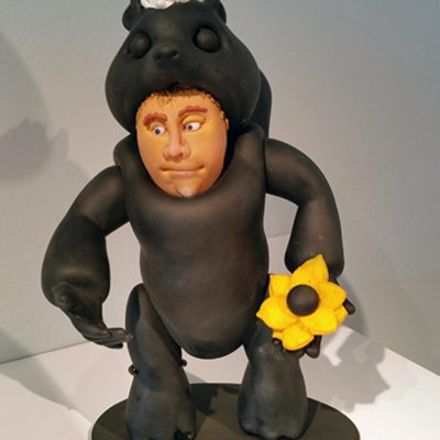 Sculpted glass person in skunk suit holding flower by Danny White